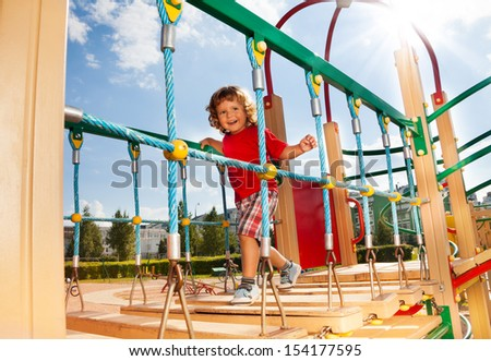 Happy running over the suspension bridge little three years old child on playground on sunny day - stock photo