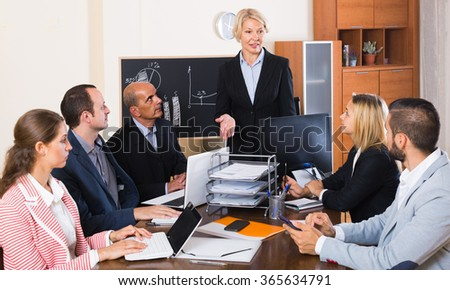 happy russian colleagues discussing price development at office - stock photo