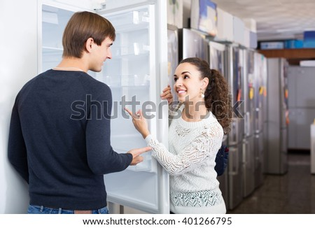 happy russian  family couple choosing new refrigerator in hypermarket
