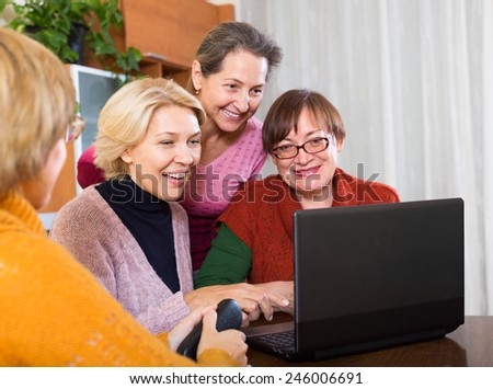 Happy russian female pensioner studying laptop  at home - stock photo