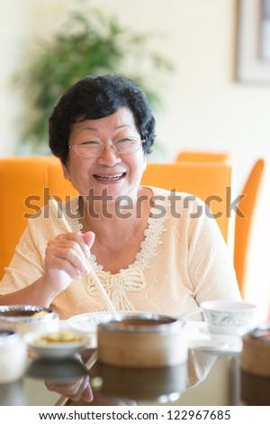 Happy 60s Senior Asian Woman dining indoors - stock photo