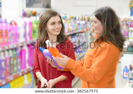 Happy sales woman showing some cleaning product in supermarket - stock photo