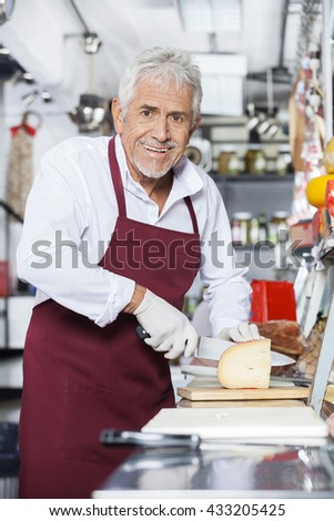 Happy Salesman Slicing Cheese In Store - stock photo