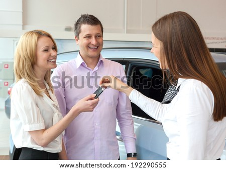 Happy saleswoman handing over car keys to the attractive young family