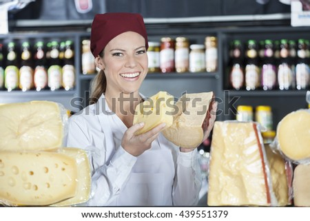 Happy Saleswoman Holding Fresh Cheese In Store - stock photo