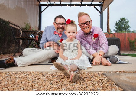 Happy same sex couple sitting with daughter outdoors - stock photo