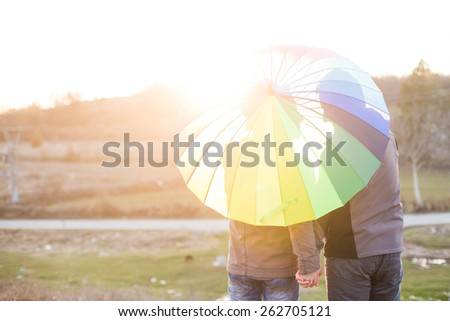 Happy same sex couple under rainbow umbrella - stock photo
