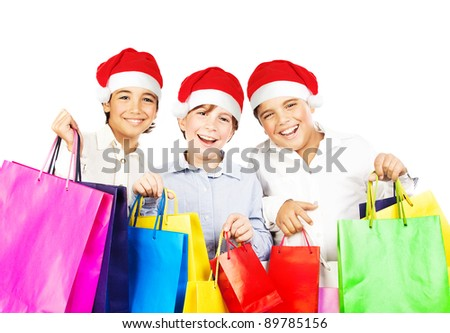 Happy Santa boys with gifts, kids carrying colorful shopping bags with Christmas presents isolated over white background, smiling preteen friends in red hats having fun, celebrating holidays - stock photo