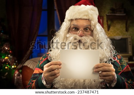 Happy Santa Claus holding a greeting card with blank copyspace and smiling at camera - stock photo