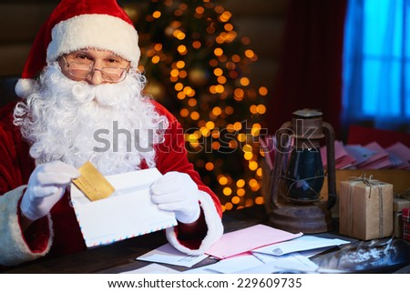 Happy Santa Claus looking at camera while putting discount card into envelope