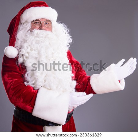 happy Santa Claus shows gesture. on gray background - stock photo