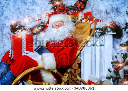 Happy Santa Claus sitting in a rocking chair with a gift box. He is in a beautiful room with Christmas tree.