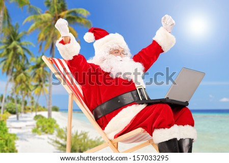 Happy Santa Claus sitting on a chair with laptop and gesturing happiness, on a tropical beach - stock photo