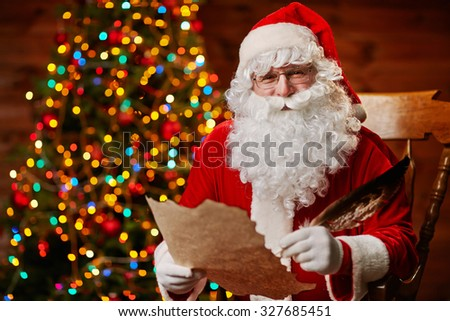 Happy Santa Claus with feather and Christmas letter - stock photo