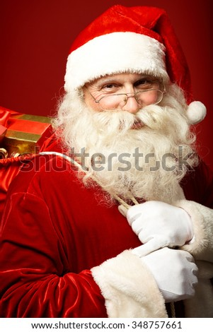 Happy Santa Claus with sack of presents looking at camera - stock photo