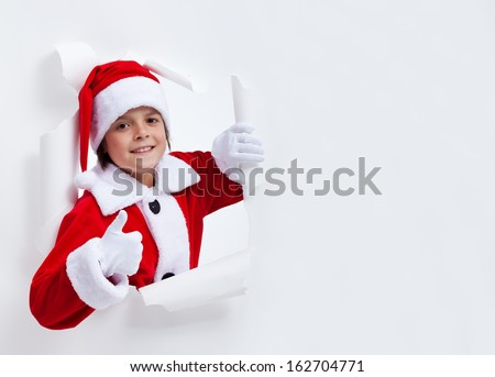 Happy santa costume boy leaning through paper hole - giving thumbs up sign, with copy space - stock photo