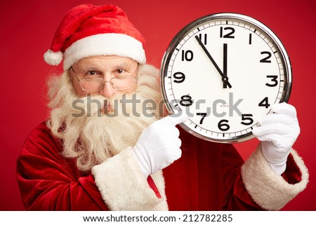 Happy Santa in eyeglasses pointing at clock showing five minutes to Christmas - stock photo