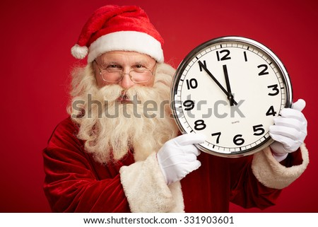 Happy Santa showing at clock showing five minutes to Christmas night - stock photo