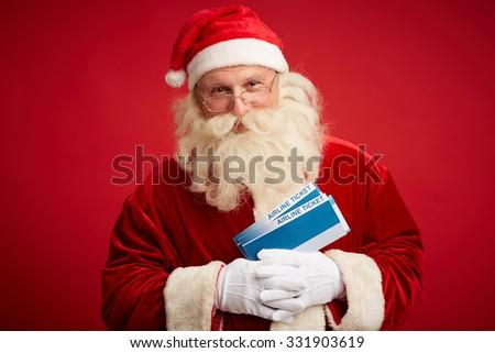 Happy Santa with air tickets looking at camera - stock photo