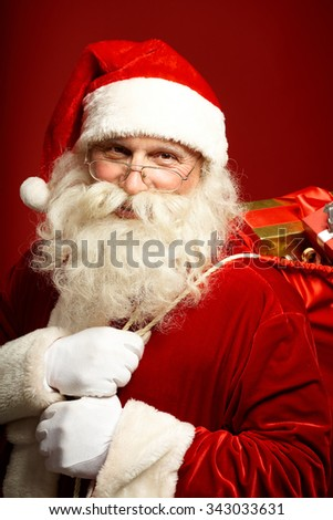 Happy Santa with sack full of Christmas presents - stock photo