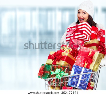 Happy Santa woman with Christmas gift over shopping mall background. - stock photo