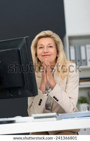 Happy satisfied businesswoman with long blond hair sitting at her desk with her hands clasped and a pleased expression smiling at the camera - stock photo