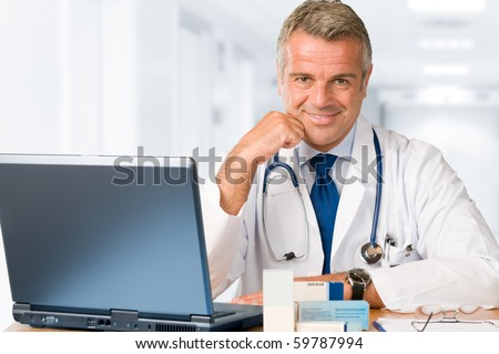 Happy satisfied mature doctor working and looking at camera in his modern clinic office - stock photo