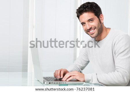 Happy satisfied young man working on laptop and looking at camera - stock photo