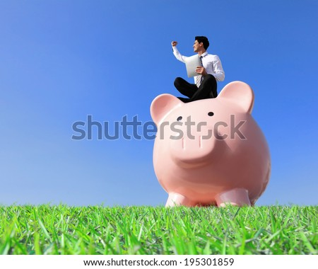 Happy Saving Money with my piggy bank - Young business man sitting on piggy bank with touch pad - stock photo