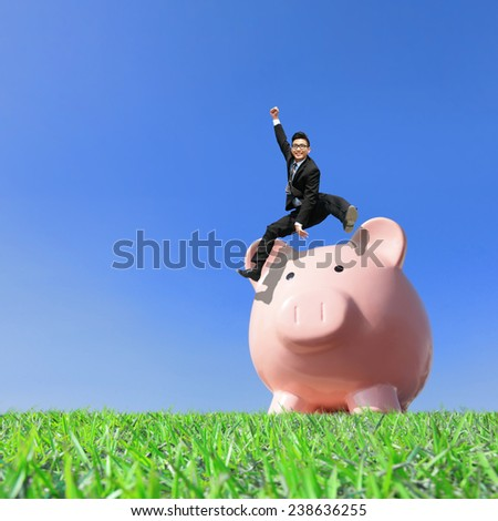 Happy Saving Money with my piggy bank - Young excited business man jump over piggy bank - stock photo