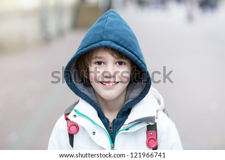 Happy school boy walking on a street with a backpack on a cold day - stock photo