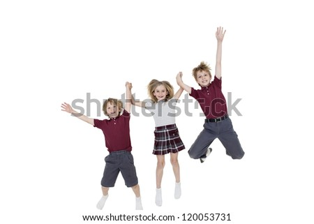 Happy school children holding hands while jumping over white background