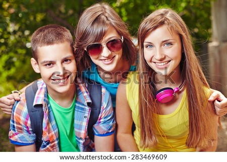 Happy school friends in casualwear looking at camera outside