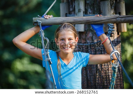 Happy school girl enjoying activity in a climbing adventure park on a summer day - stock photo