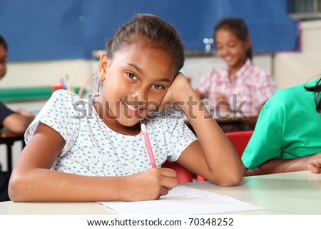 Happy school girl with beautiful smile in class - stock photo