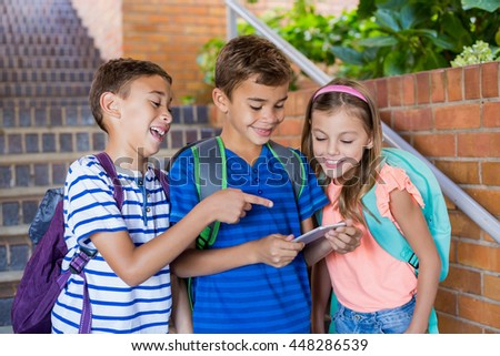 Happy school kids looking at mobile phone at school - stock photo