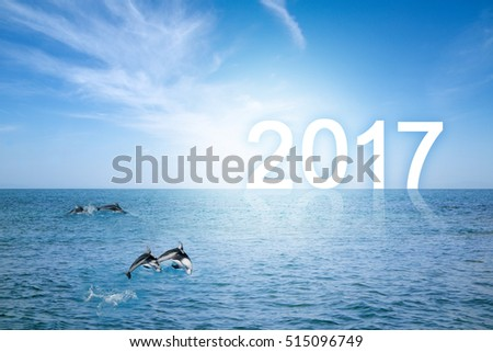Happy school of bottlenose dolphins jumping over sea waves with happy new year background. The Number 2017 standing on Horizon with clear blue sky and surface of sea. Happy New Year conceptual image.
