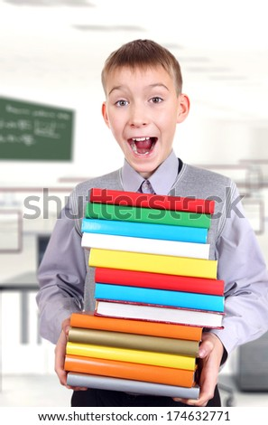 Happy Schoolboy holding the pile of the Books in the Classroom - stock photo