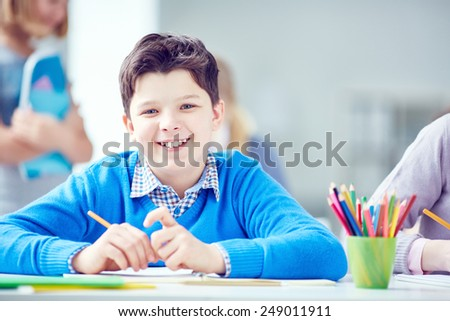 Happy schoolboy in casualwear sitting at lesson