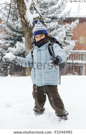 happy schoolboy kid wearing warm clothes in snow