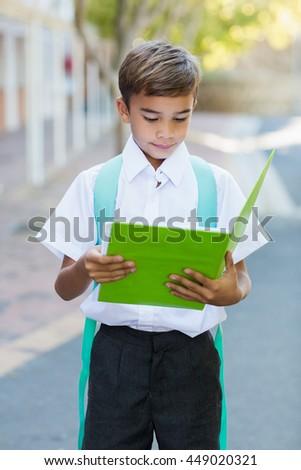 Happy schoolboy reading book in campus at school - stock photo