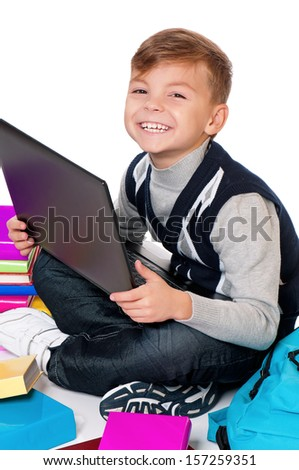 Happy schoolboy sitting on floor with books and laptop on white background