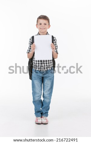 Happy schoolboy with notebook isolated on white background. Cute boy showing blank sheet and smiling - stock photo