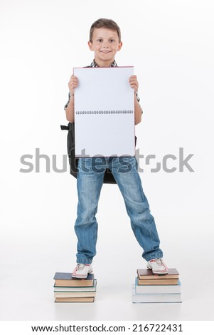 Happy schoolboy with notebook isolated on white background. Cute boy showing blank sheet on stack of books - stock photo