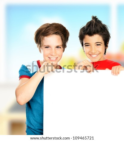 Happy schoolboys in the classroom, cheerful preteen boys students holding white blank board with copy space for ad text, teen friends smiling, kids studying at school, children education concept - stock photo