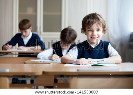 Happy schoolboys sitting at desk, classroom - stock photo