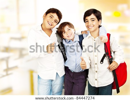 Happy schoolboys with thumbs up, back to school, boys best friends and classmates hugging, smiling, at the classroom, teenage education concept