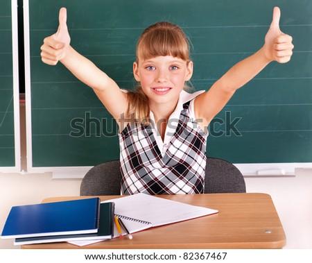 Happy schoolchild in classroom near blackboard. - stock photo