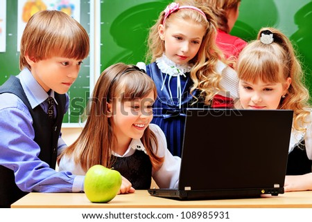Happy schoolchildren at a classroom during the lesson. Education. - stock photo