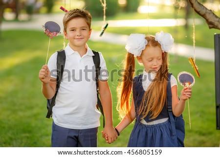 Happy schoolchildren with backpacks outdoors - stock photo